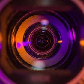 Video camera lens lit in orange and purple