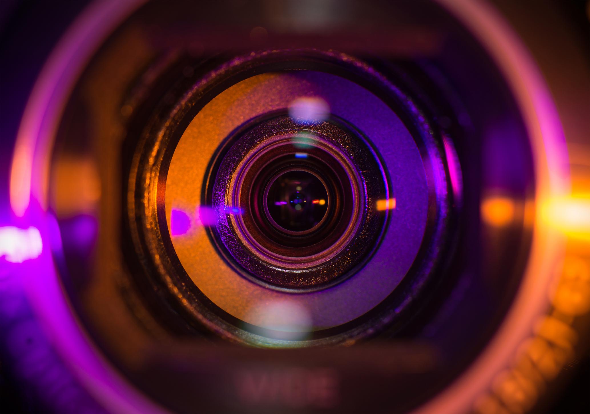 Video camera lens lit in orange and purple