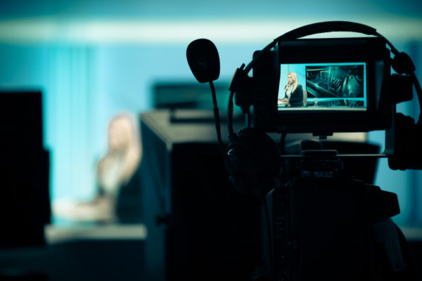 Young beautiful blonde television announcer at studio during live broadcasting.Female TV director at editor in studio.Recording at TV studio with television anchorwoman. TV NEWS studio with camera